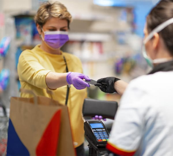 Store cashier returning credit card to woman wearing medical mask and gloves